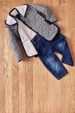 Jeans e rivestimento del ` s dei bambini su fondo di legno Fotografia Stock