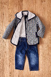Jeans e rivestimento del ` s dei bambini su fondo di legno Immagine Stock