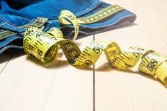 Jeans e un nastro di misurazione Concetto di allentare peso frutti per perdita di peso Immagine Stock