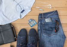 Jeans ed accessori del ` s degli uomini sul pavimento di legno Immagine Stock