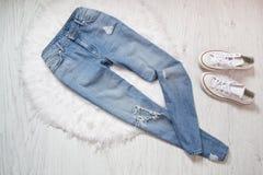 Jeans en lambeaux bleus et espadrilles blanches sur la fourrure blanche fashionable Photo stock