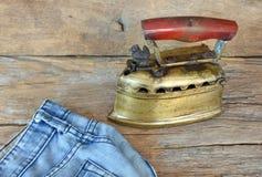 Jeans en uitstekend stijl vlak die ijzer door houtskool wordt verwarmd Stock Foto