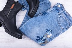 Jeans en vrouwelijke zwarte leerschoenen op witte houten achtergrond De kleren van de vrouwen` s manier Stock Foto's