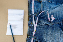 Jeans et bande de mesure, bloc-notes, crayon sur la table en bois Photo libre de droits