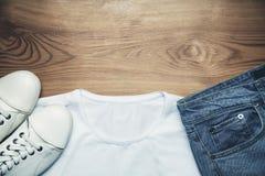 Jeans et chemise blancs d'espadrilles sur le fond en bois Photographie stock libre de droits