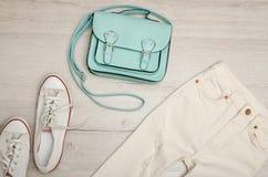 Jeans et espadrilles blancs, sac en bon état concept à la mode Fond en bois Images stock