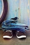 Jeans et espadrilles sur un fond de barrière en bois bleue Image libre de droits