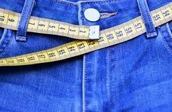 Jeans et plan rapproché de mesure de bande, concept de mode de vie sain et poids de perte images stock