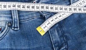 Jeans för en blåttkvinna och linjalen, begrepp av bantar och viktförlust Jeans med att mäta bandet Sund livsstil som bantar, kond Arkivfoton