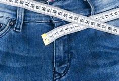 Jeans för en blåttkvinna och linjalen, begrepp av bantar och viktförlust Jeans med att mäta bandet Sund livsstil som bantar, kond Fotografering för Bildbyråer
