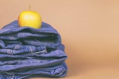 Jeans för kvinna` s vek i en hög och överst av Apple, på en kulör bakgrund Gjort i en tappningkapacitet Royaltyfri Bild