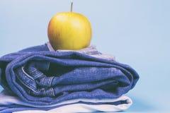 Jeans för kvinna` s vek i en hög och överst av Apple, på en kulör bakgrund Gjort i en tappningkapacitet Fotografering för Bildbyråer