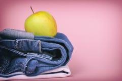 Jeans för kvinna` s vek i en hög och överst av Apple, på en kulör bakgrund Gjort i en tappningkapacitet Arkivbilder