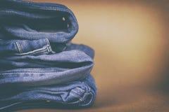 Jeans för kvinna` s vek i en hög på en kulör bakgrund Gjort i en tappningkapacitet Royaltyfri Foto