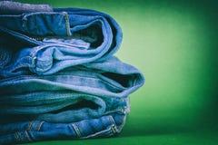 Jeans för kvinna` s vek i en hög på en kulör bakgrund Gjort i en tappningkapacitet Arkivfoton