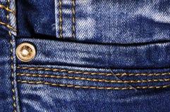 Jeans fabric closeup. With seams and metal pin Royalty Free Stock Photos