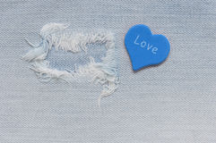 Jeans fabric torn with a blue heart and a word love. Stock Images