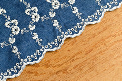 Jeans fabric with white flower embroidery laid over plywood back. Jeans fabric with white flower embroidery laid over plywood Royalty Free Stock Photography