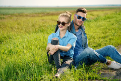 Jeans fashion. Hitchhiking couple. Happy young people sitting by the highway Royalty Free Stock Images