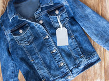 Jeans female jacket on wooden background with tag label. Stock Photo