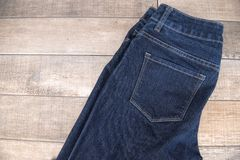 Jeans foncés placés sur un plancher en bois Image stock