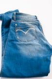 Jeans gefaltet auf weißem Hintergrund stockfotografie