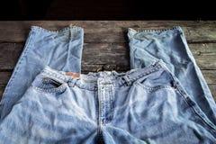 Jeans gestapelt auf einem hölzernen Hintergrund Lizenzfreies Stockbild