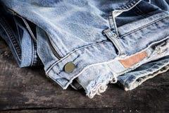 Jeans gestapelt auf einem hölzernen Hintergrund Stockbilder