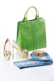 Jeans, green sandals and green leather handbag. Isolated Royalty Free Stock Image