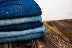 Jeans häufen auf hölzernem Brett an Stockfotos