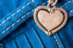 Jeans heart. Macro shot of blue jeans with metal heart detail Royalty Free Stock Images