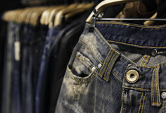 Jeans on hungers in store Stock Photo