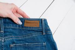 Jeans i kvinnlig hand f?r begreppsframsida f?r sk?nhet bl? ljus kvinna f?r makeup f?r mode close upp arkivbild