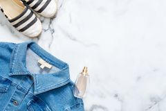 Jeans jacket, bottle of perfume, striped summer sandals on marble background. Flat lay design composition with retro fashioned fem. Inine clothing and royalty free stock image