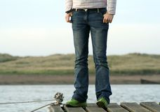 Jeans on the Jettty. Teenager stands on the edge of the jetty watching for her fathers boat Royalty Free Stock Photography