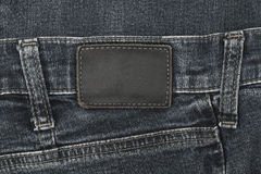 Jeans label sewed on black jeans. Leather jeans label sewed on black jeans stock images
