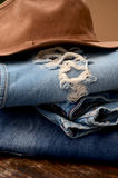 Jeans and Leather Hat. Fashion Torn Jeans and Leather Hat royalty free stock photos