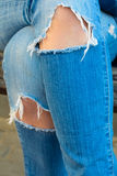 Jeans loqueteux Les genoux femelles des jambes, jetés au-dessus de l'un l'autre photo libre de droits