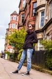 Jeans maigres bleus de port modèles, espadrilles noires et lunettes de soleil Image libre de droits