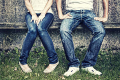 Jeans. Male and female in jeans sitting on a bench Stock Image