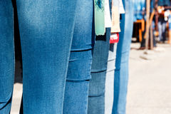 Jeans on market. Row of mannequins with different coloured jeans on market. Some outwear examples in a line before shop. Clothes sale concept. Pants on dummies Stock Photo