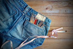 Jeans with measure and crayons, paintbrush in back pocket on wooden Royalty Free Stock Image
