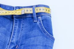 Jeans and measuring subject for weight loss on blue background.  royalty free stock photos