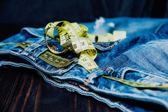 Jeans and measuring subject for weight loss. Jeans and centimeter on a wooden background. clothing stock images
