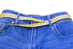 Jeans and measuring subject for weight loss on white background.  stock images
