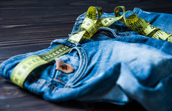 Jeans and measuring subject for weight loss. On wooden background stock image