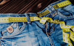 Jeans and measuring subject for weight loss. On wooden background royalty free stock photo
