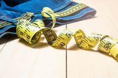 Jeans and a measuring tape.Concept of loosing weight.fruits for weight loss Stock Image