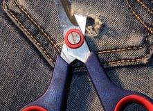 Jeans met een paar van schaar om een gat in de zak te snijden Stock Fotografie