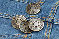 Jeans metal buttons on denim. Royalty Free Stock Photo
